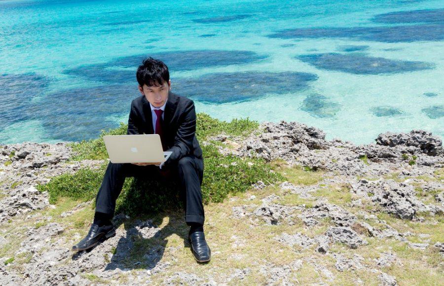 海辺でパソコン作業をするノマドワーカー