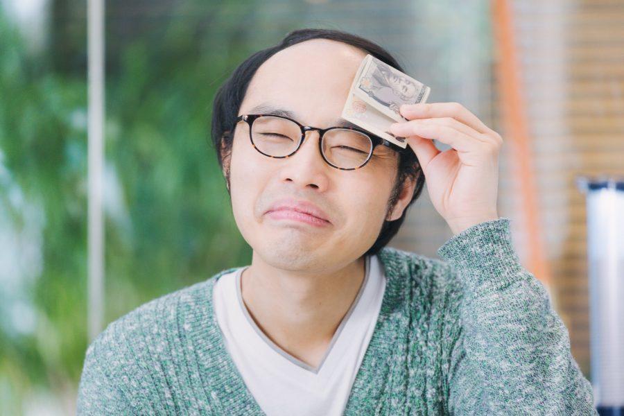 お金で汗を拭く男性